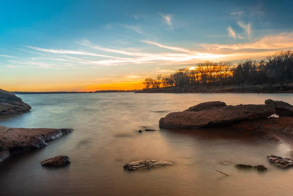 USA - Oklahoma - Edmond - Lake Arcadia Lakeside sunset with large red rocks and lake in foreground