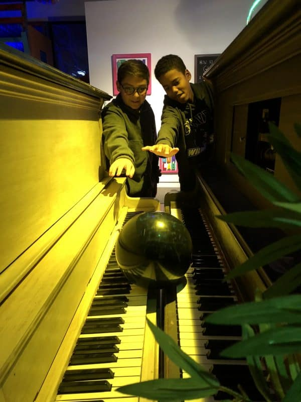 Boys playing with 'Bowling Ball Pianos' in THE EXPERIENCE. Art by David Reed James, courtesy ahha Tulsa.