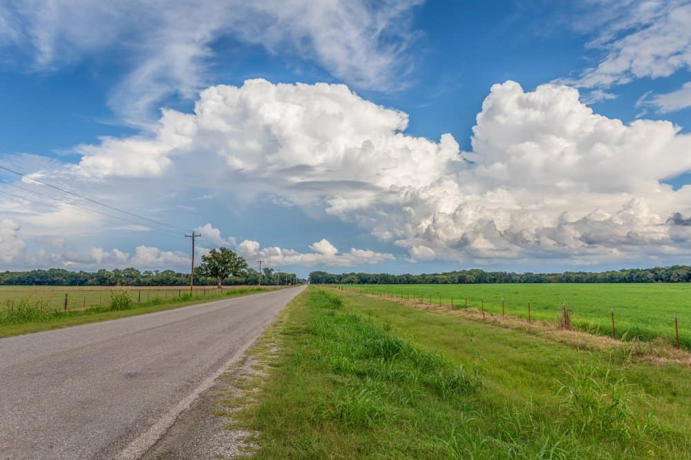 Oklahoma - Country road in Oklahoma with white clouds against a blue sky.