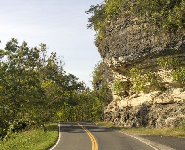 Oklahoma - Driver view of 2-lane curved road beside large rock cliff
