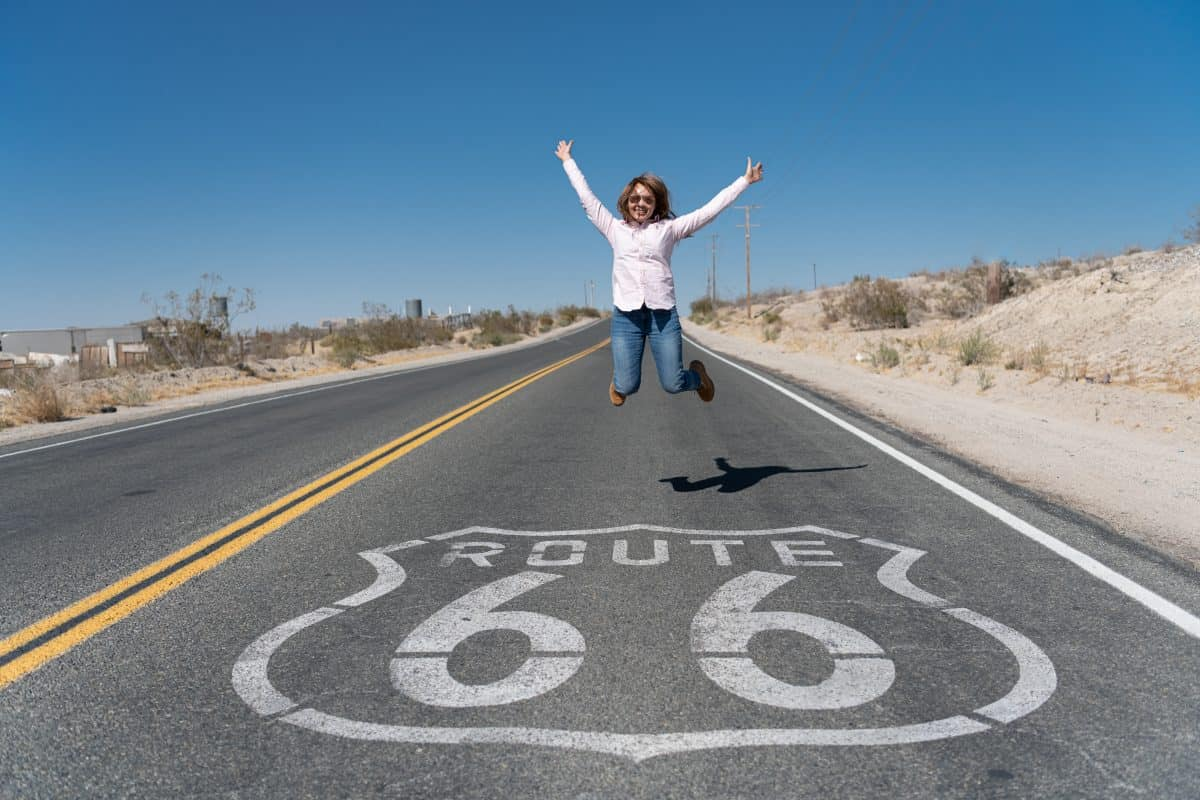 Woman Jumping on Highway sign for Route 66 on asphalt of country road