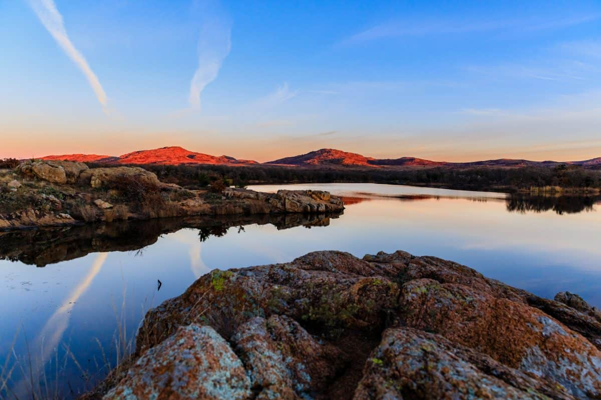 The sky and rocky edge reflects in the still water in the early morning at Wichita Mountains National Wildlife Refuge, November 2017 Oklahoma