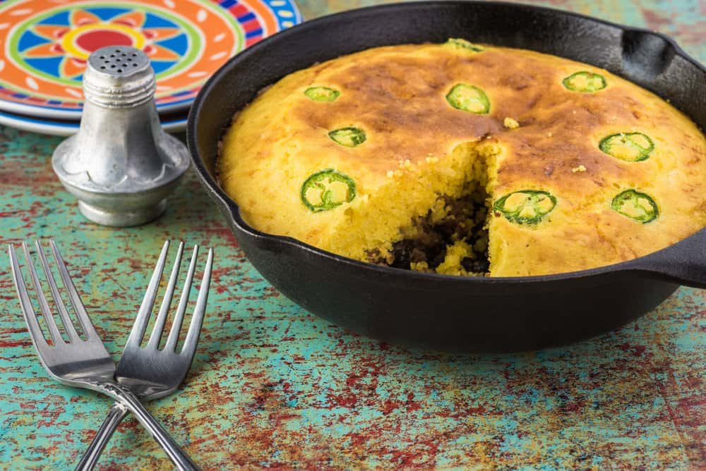 Fresh baked homemade cut beef tamale pie in iron skillet.