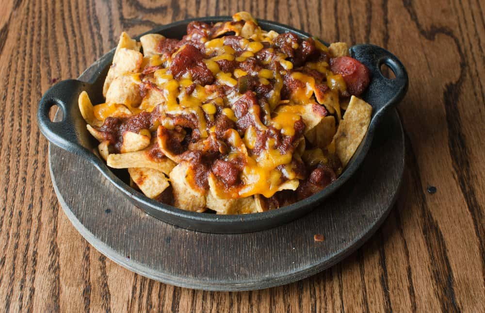 Frito chili pie made with corn chips, spicy Texas chili melted cheddar cheese and garnishes.