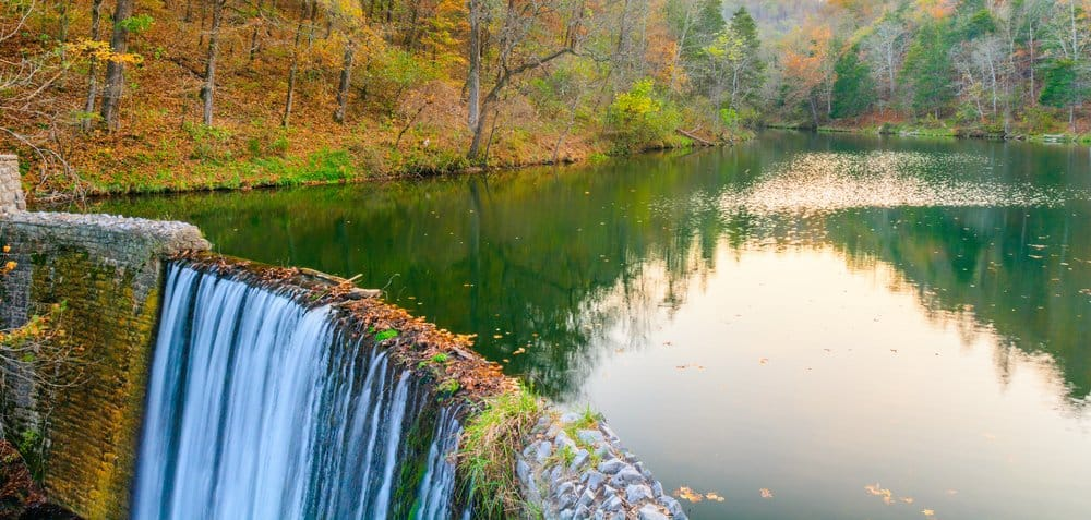 USA - Arkansas - Beautiful, clear and tranquil water falls over the edge of a man made dam into a man made waterfall at Mirror Lake, located at Blanchard Springs, Arkansas surrounded by red and yellow fall colors.