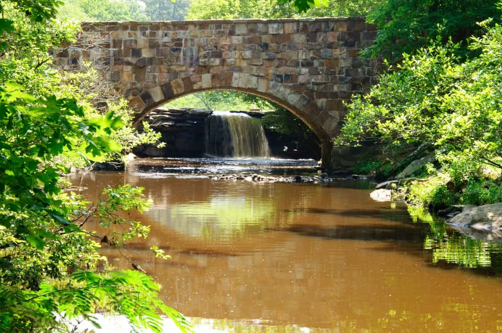 Arkansas - Conway - stone bridge, waterfall and muddy creek