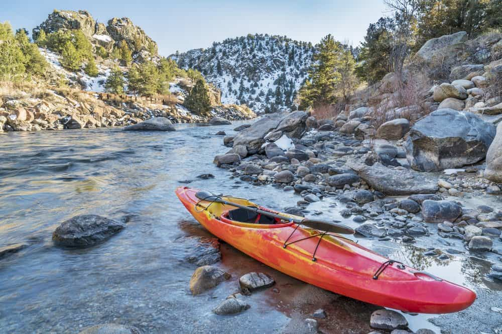 USA - Arkansas - whitewater kayak with a paddle on a river shore - Arkansas River, Colorado in winter scenery