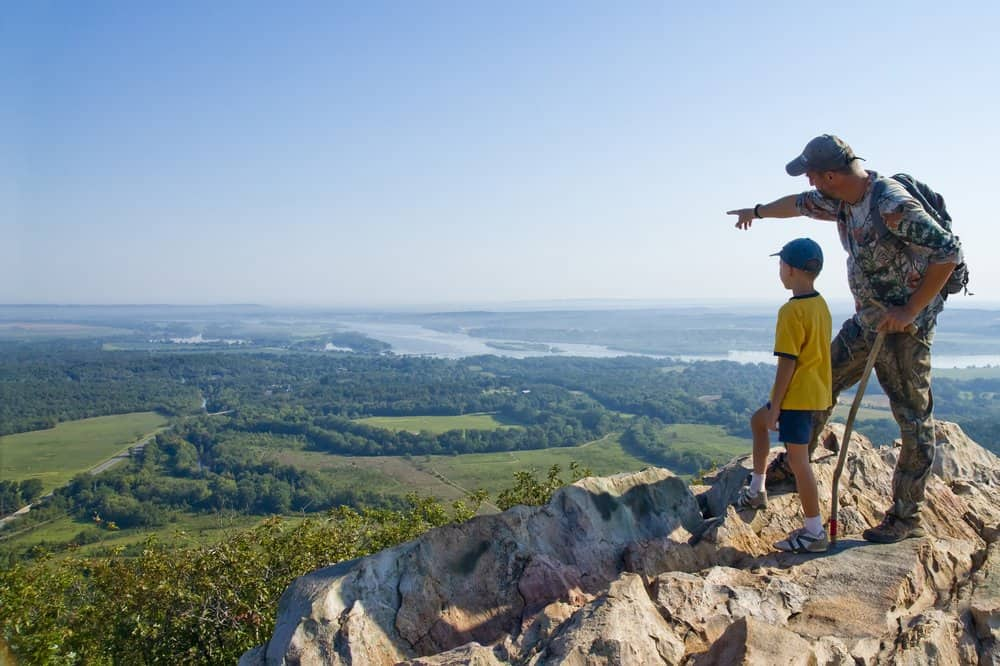 USA - Adult and child standing on a mountaintop near the Arkansas River. The father shows his son the sights