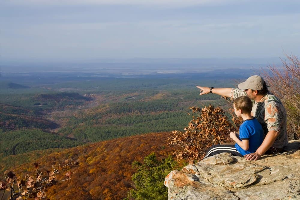 USA - Arkansas - Father and son on a mountain top. A man shows at the landscape