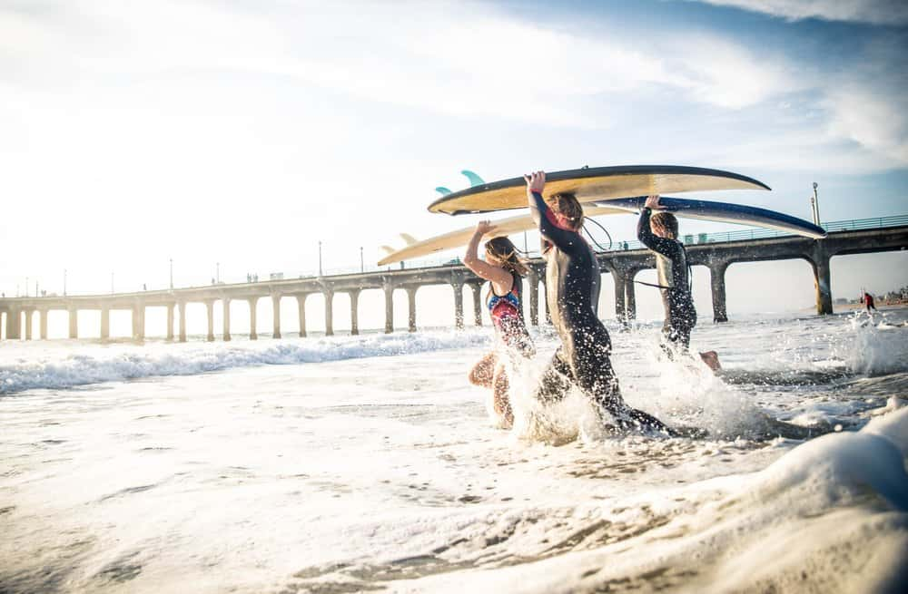 California - Group of friends going to surf at the beach