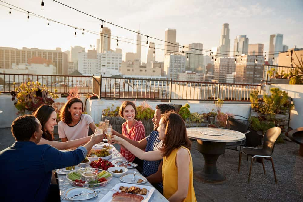 California - Friends Gathered On Rooftop Terrace For Meal With City Skyline In Background