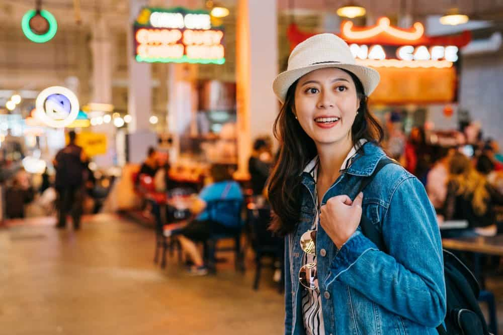 USA - California - hungry tourist joyfully standing in the market food court and finding lunch to eat. young attractive woman on vacation standing in restaurant. Asian lady solo los angeles trip.
