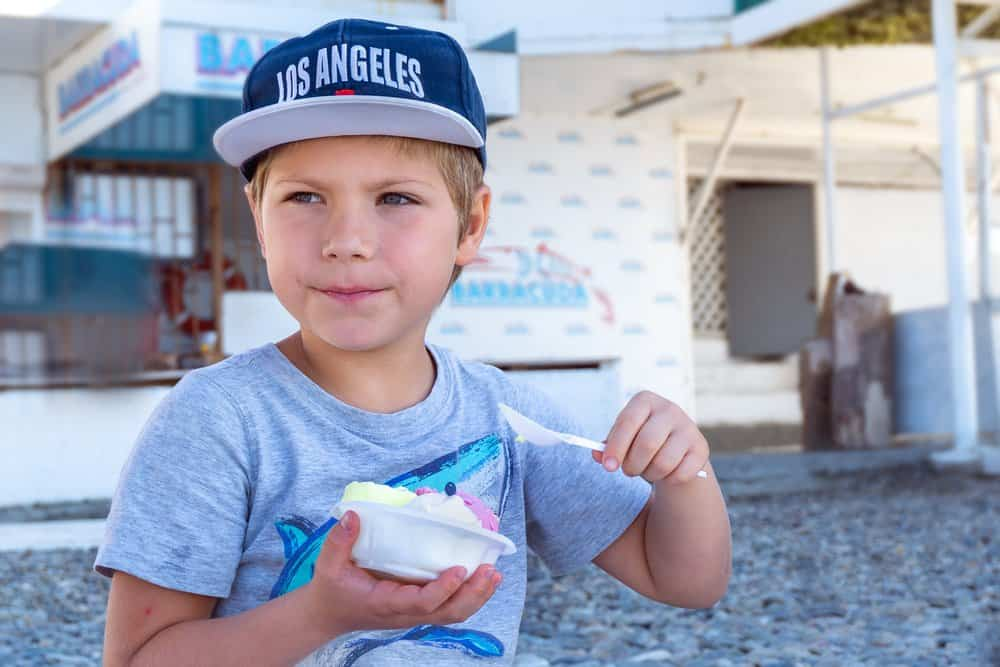 """California - Los Angeles - Boy six years old in cap with sign """" Los Angeles"""" eating ice cream at the beach"""