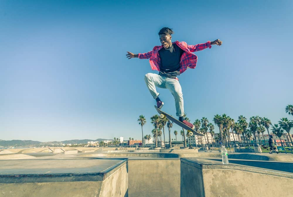 California - Los Angeles - Skateboarder jumping over a gap in a skate park - Young man attempting a trick with his skate