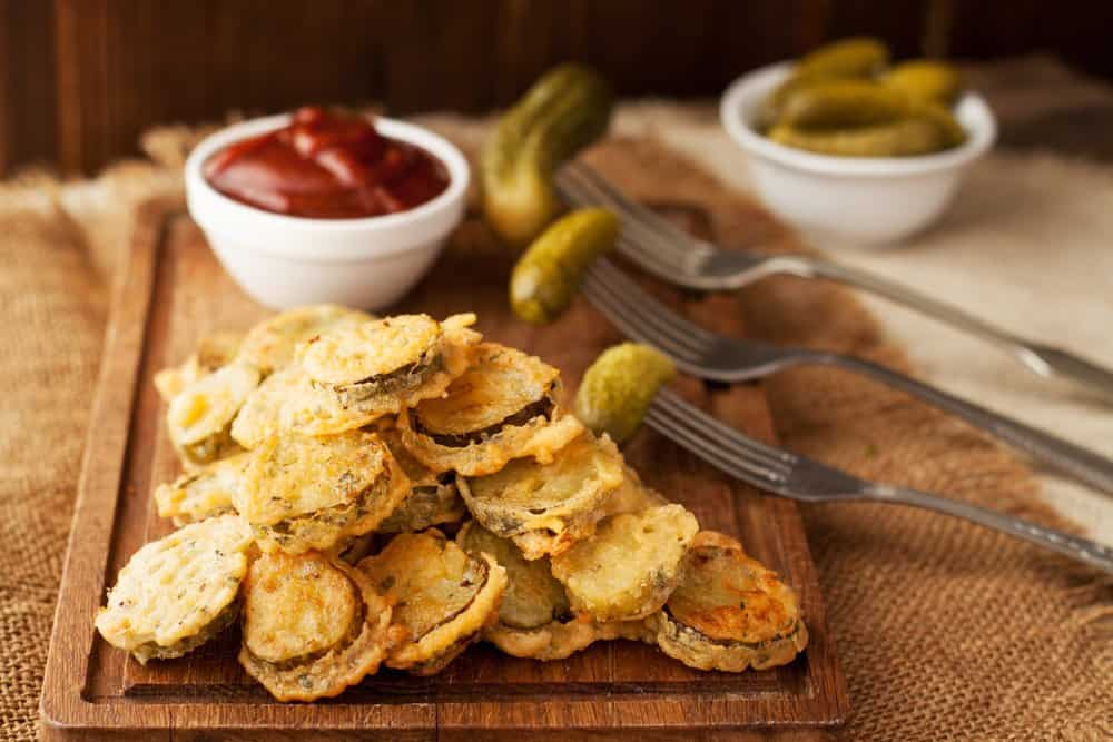 Arkansas - Arkansas cuisine - Battered fried pickles with ketchup dipping sauce on wooden board