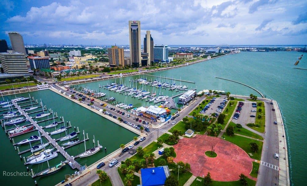 Texas - Corpus Christi Texas Skyline view of City harbor bridge in background with many rows of piers filled with boats and sailboats and yachts across the summer vacation landmark getaway