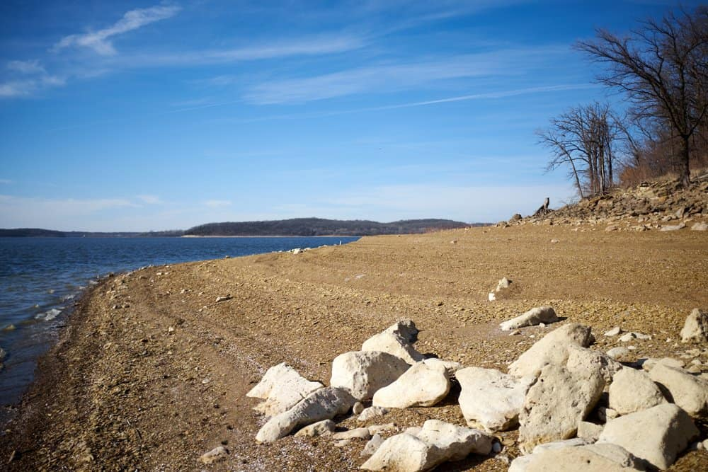 Kansas - Shoreline of Lake Perry Kansas in evening light with a cluster of large rocks and boulders in the foreground and leafless winter trees under a blue sky