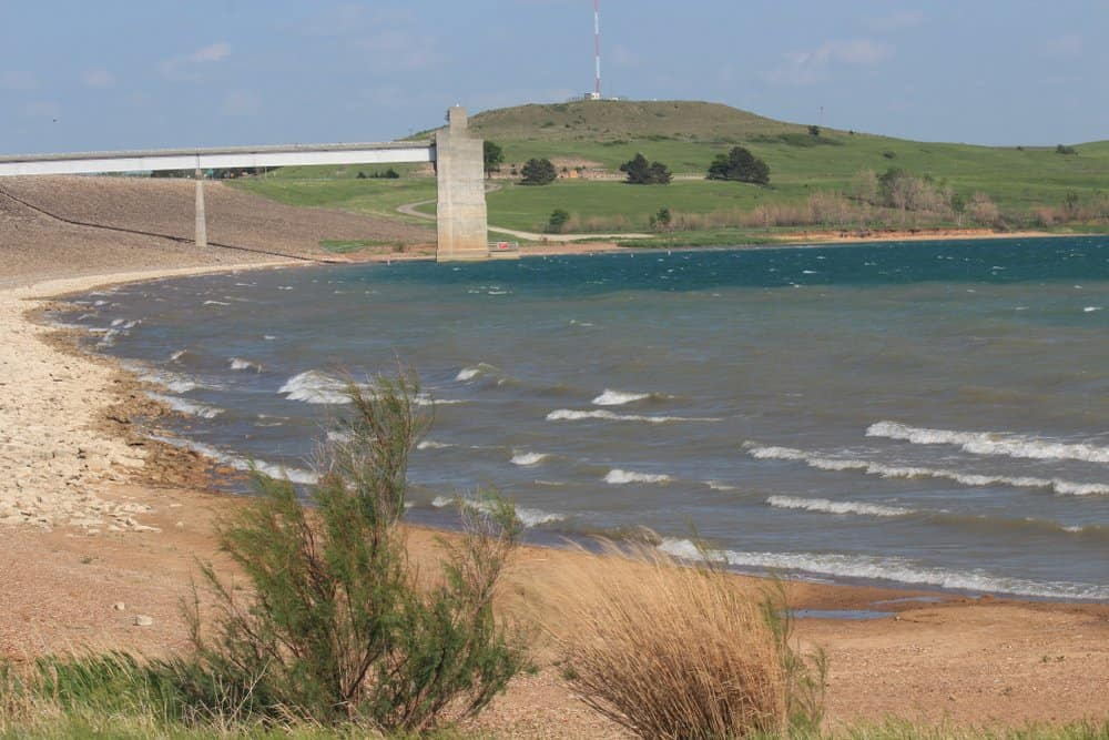 A shot of Wilson Reservoir with blue water,sand,white caps on the water,and a beach with the dam and tower in the back ground . At Wilson Reservoir (Lake). that's south of Lucas Kansas USA.