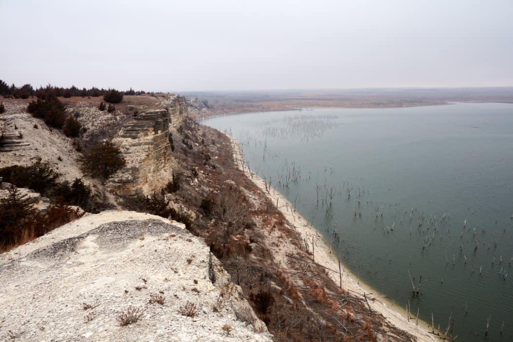 Kansas - Cedar Bluff State Park - View from the limestone bluff of Cedar Bluff Reservoir, Kansas, on a misty day with the skeleton trunks of drowned trees protruding from the water