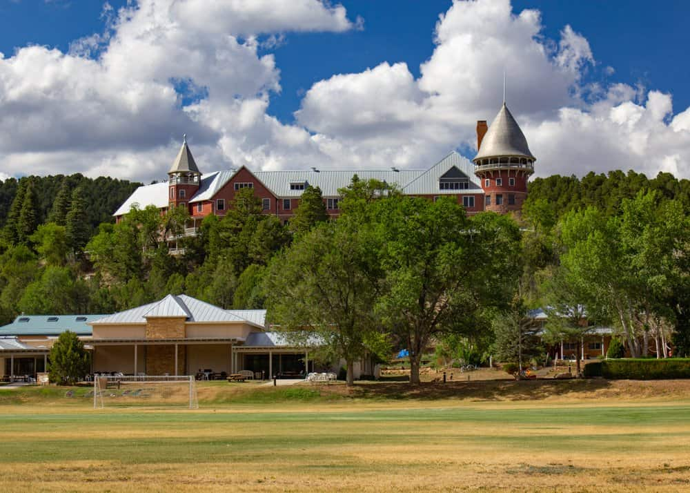New Mexico - A historic castle on a hill with trees surrounding it, a playing field in the foreground and a bright blue cloudy sky in the background.