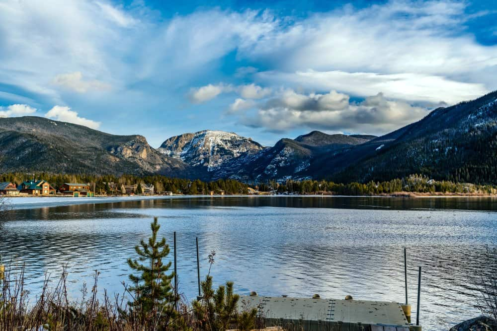 Colorado - Grand Lake - Views of the Rocky Mountains snow covered mountain tops from across a still smooth lake with majestic clouds overhead in Grand Lake, Colorado, USA.