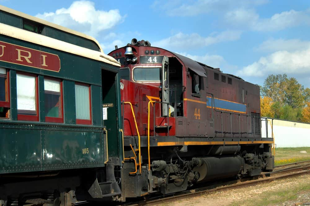 Arkansas - Van Buren - Arkansas and Missouri Railroad begins Ozark Mountain tour with engine and passenger cars. Engine is maroon and pullman is green.