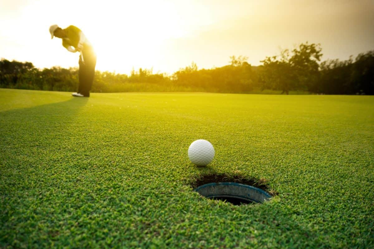 Arkansas - Hardy - Golfer putting golf ball on the green golf, lens flare on sun set evening time.