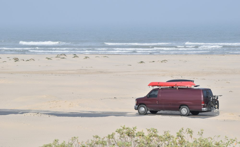 Texas - Large red van with orange kayaks on top and mountain bikes on the back parked on the beach on South Padre Island, Texas.