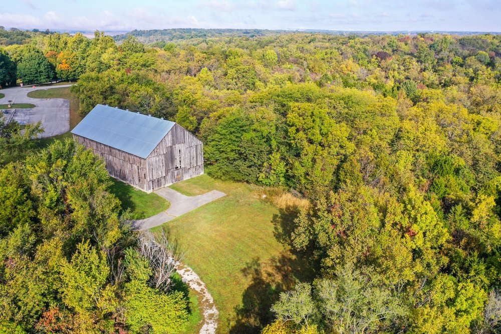 Missouri - Weston - Aerial drone photo of an old, historic, tobacco barn in the public Weston Bend State Park in Missouri north of Kansas City. Trees are just getting their fall colors.