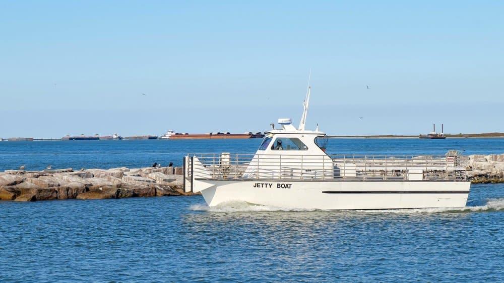 Texas - PORT ARANSAS, TX - 27 FEB 2020: Jetty boat leaves the marina entrance on a sunny day as it goes to retrieve passengers from San Jose Island.